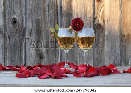 Red rose on a glass of white wine  on a wooden background - stock photo
