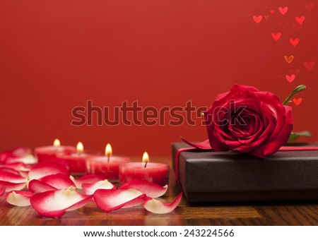 Red rose over  box of chocolate with candles and flower petals a romantic hearts on side - stock photo