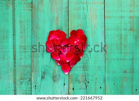 Red rose petals in the shape of heart on weathered antique green wood background - stock photo