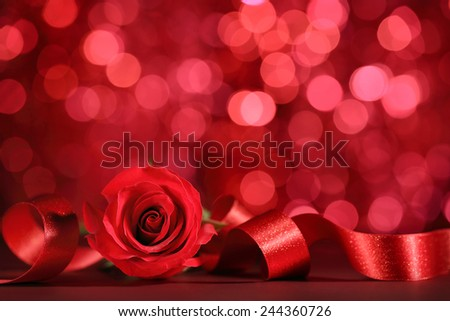 Red rose with ribbon on bokeh background - stock photo