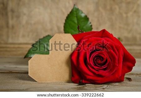 Red rose with valentine for text on wooden background - stock photo