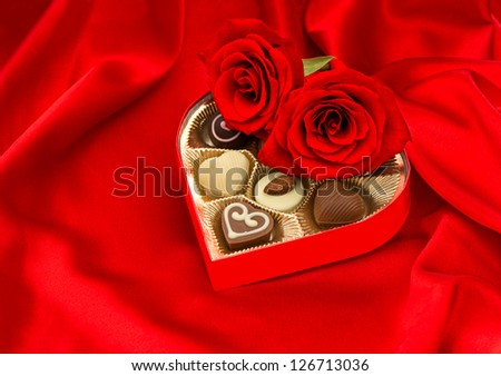 red roses and assorted chocolate pralines in golden heart shaped gift box on satin background - stock photo