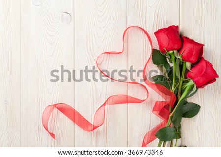 Red roses and heart shape ribbon over wooden table. Valentines day background. Top view with copy space - stock photo