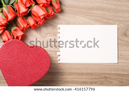 Red roses and Valentine's day Gift Box hearts on wooden background. Top view with copy space - stock photo