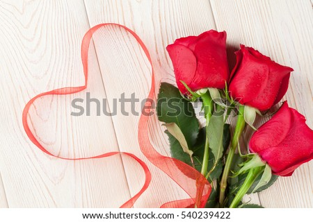 Red roses and Valentine's day heart on wooden background. Top view