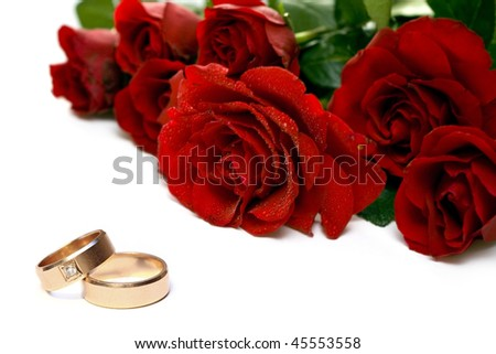 Red roses and wedding rings isolated on white - stock photo