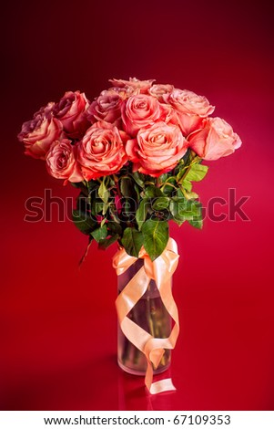 Red roses bouquet in glass vase isolated on red background - stock photo