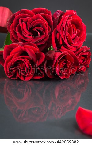 Red roses bouquet with ribbon on dark mirror table
