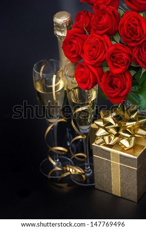 red roses, golden gift and and champagne on black background. festive flower arrangement. selective focus - stock photo