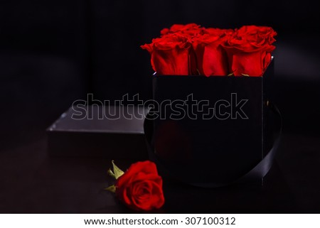 Red roses in a black box on the table. A perfect gift for ...