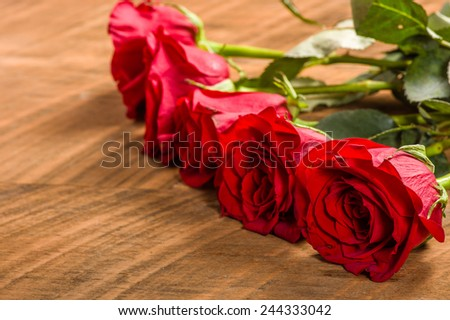 Red roses in a row on wooden table - stock photo