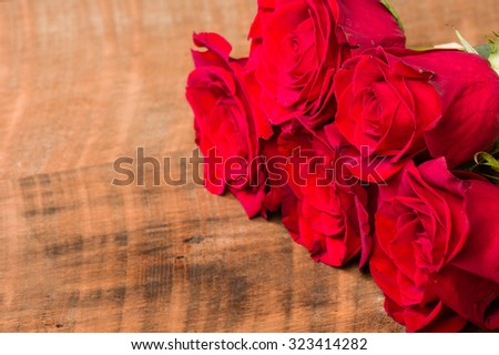 Red roses in bloom on table with room for text - stock photo
