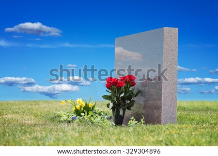 Red roses in grass with reflection in tombstone on graveyard, blue sky in background