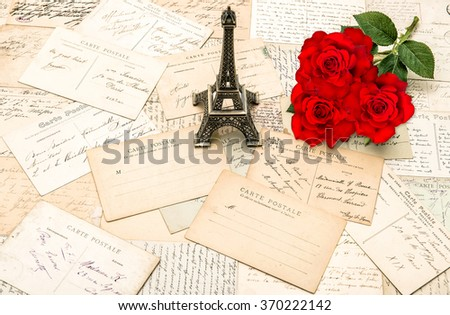Red roses, old letters and souvenir Eiffel Tower from Paris. Nostalgic holidays background