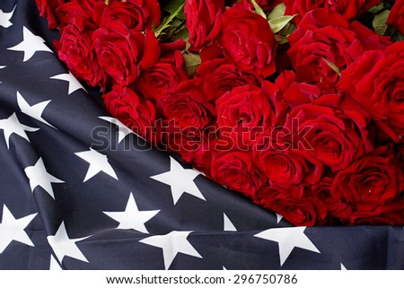 Red roses on american flag. Memory - stock photo