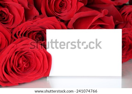 Red roses on Valentine's or mothers day with empty card and copyspace for your own text - stock photo