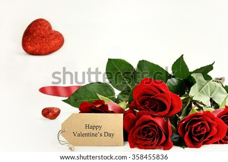 Red roses with an Happy Valentines Day label and glitter hearts in the background. Room for copy space with extreme shallow depth of field.