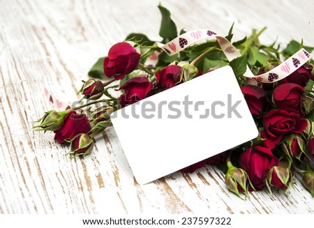Red roses with greeting card on a wooden   background