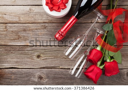 Red roses with Valentines day gift and champagne over wooden background. Top view with copy space  - stock photo
