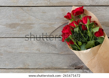 Red roses wrapped in paper on wooden table background - stock photo