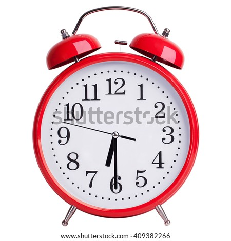 Red round alarm clock shows half of the seventh - stock photo