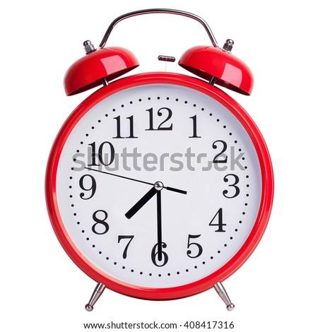 Red round alarm clock shows half past seven - stock photo