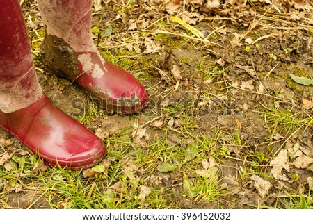 Red rubber boots on muddy grass