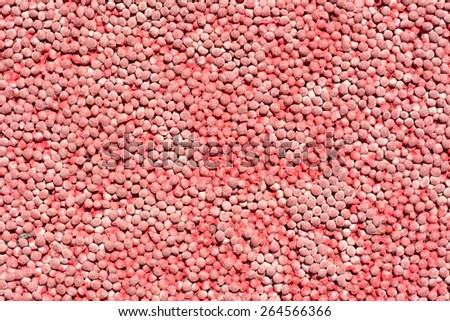 Red rubber pellets on the surface of a playground that provide texture and padding to protect children as they play. - stock photo