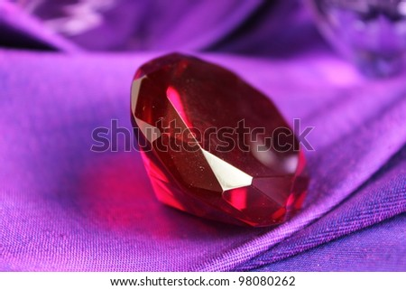 Red ruby on purple cloth - stock photo