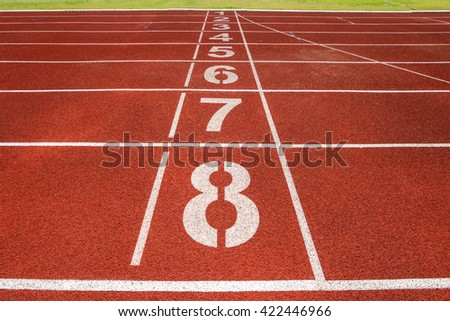 Red running track for athletics and competition with numbers - stock photo