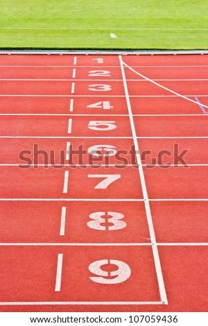 Red running tracks.Numbers one through nine. - stock photo