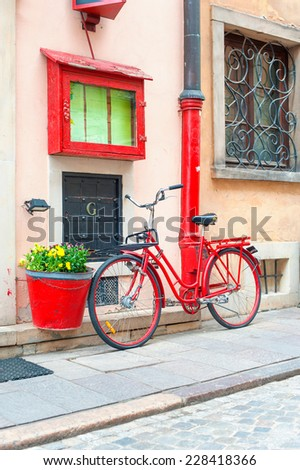 Red rustic retro bicycle close to stone wall.  Outdoors. - stock photo