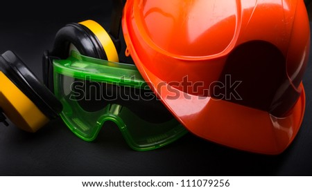 Red safety helmet with earphones and goggles - stock photo