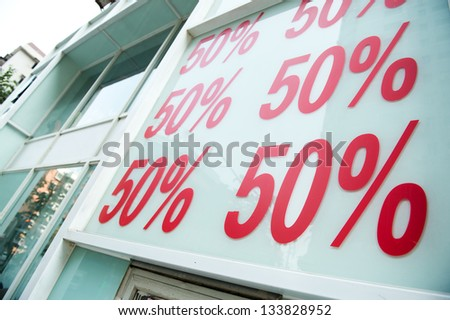 Red sale signs on shop wall, big reductions. - stock photo