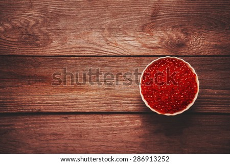 Red salmon caviar in a bowl on wooden background, top view. Space for text in left part of the image - stock photo