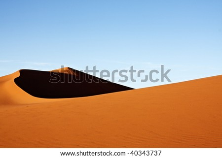 Red sand dunes with blue sky - stock photo