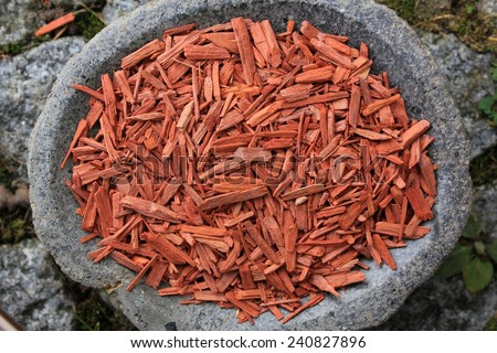 Red Sandalwood incense chips cut (santali rubri from Gabun) in a stone bowl with a natural stone pathway background - stock photo