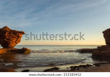 Red sandstone rocks at high tide (Green Gables Shore, Prince Edward Island , Canada) - stock photo