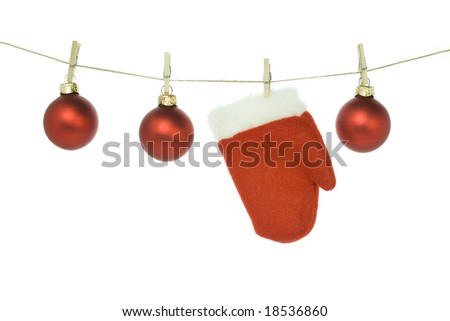 Red santa claus glove and Christmas balls on clothes line - stock photo
