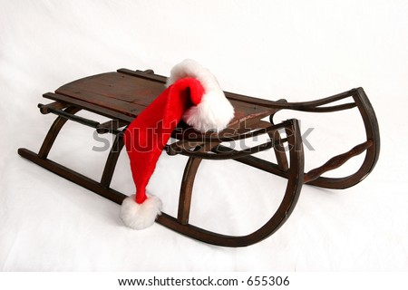 Red Santa Claus hat lying on antique wooden sled - stock photo