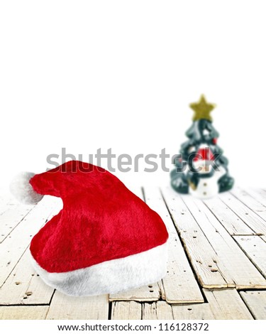 Red Santa Claus hat on a timber floor with a snowman and Christmas tree in a white background. - stock photo