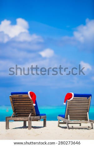 Red santa hat and Christmas stocking on chair longue at tropical white beach