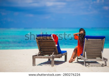 Red santa hat on chair longue at tropical white beach