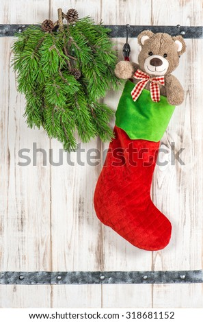 Red Santas hat, Teddy Bear and green pine tree branch. Vintage style christmas decoration