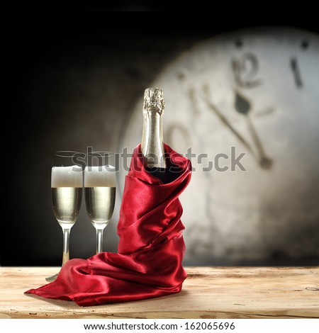 red satin champagne and clock  - stock photo