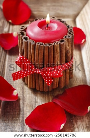 Red scented candle decorated with cinnamon sticks. Rose petals around. - stock photo