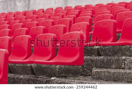 Red seats on open-air stands on football stadium - stock photo