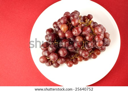 Red seedless grapes on white plate with solid red background  copy space