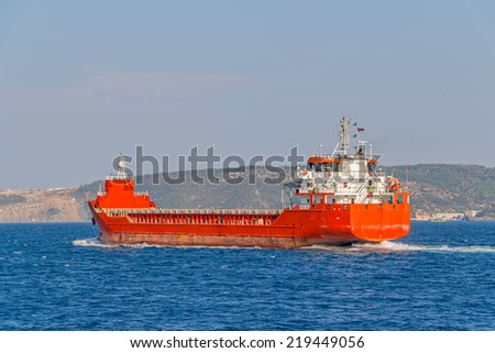 Red ship sails Bosphorus on sunny autumn day. - stock photo