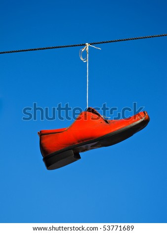 Red shoe against a blue sky. - stock photo